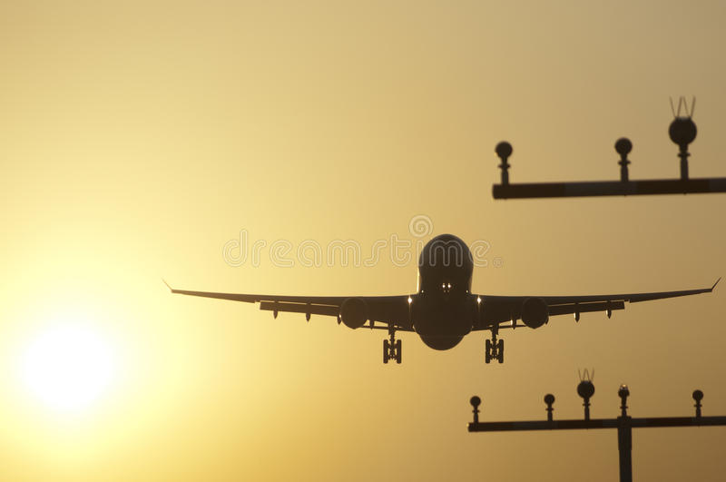 Посадка самолета на авиапорте frankfurt на восходе солнца стоковые изображения rf