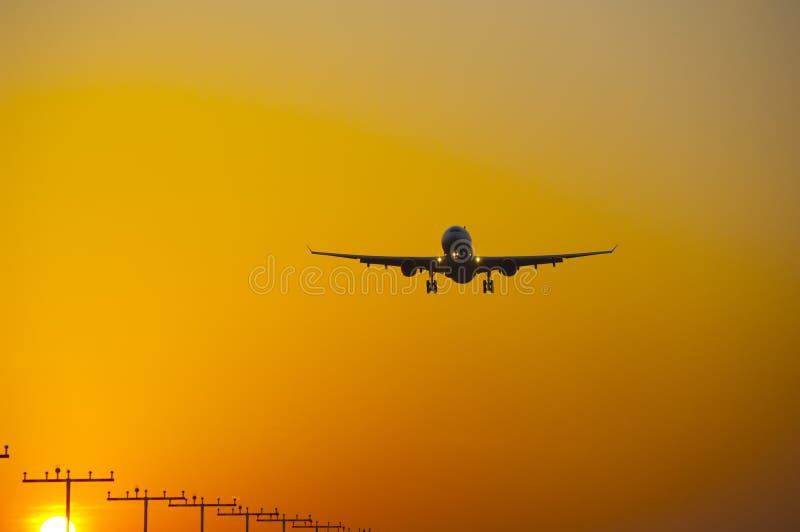 Посадка самолета на авиапорте frankfurt на восходе солнца стоковое фото rf