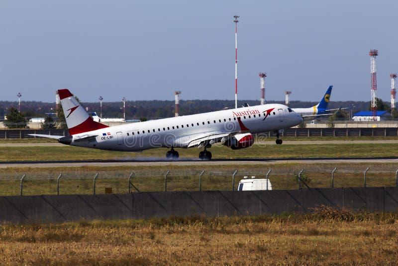 Посадка самолета Austrian Airlines Embraer ERJ-195LR на взлётно-посадочная дорожка стоковая фотография rf