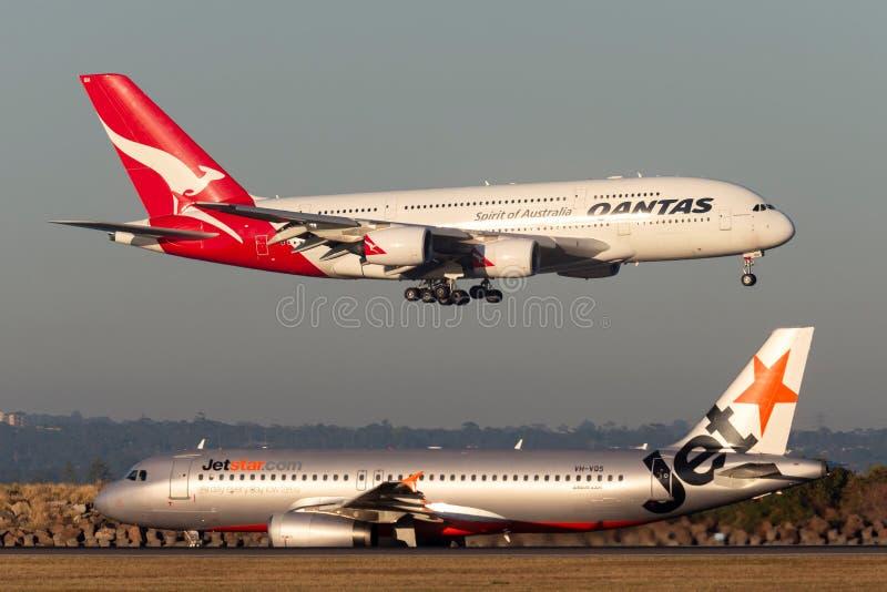 Посадка 4 engined пассажирских самолетов аэробуса A380 Qantas большая в аэропорте Сиднея пока воздушное судно Jetstar на гудронир стоковые изображения rf