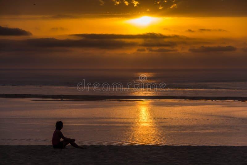 Посадочные места молодой женщины на дюне стоковые изображения
