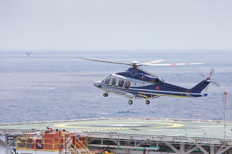Посадка вертолета на оффшорной платформе нефти и газ для того чтобы получить пассажира и груза к на берегу стоковое фото rf