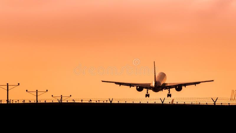 Посадка самолета двигателя на заходе солнца стоковые фото