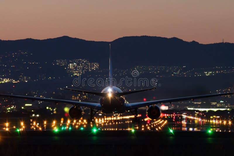 Посадка самолета к авиапорту на сумраке стоковые фотографии rf