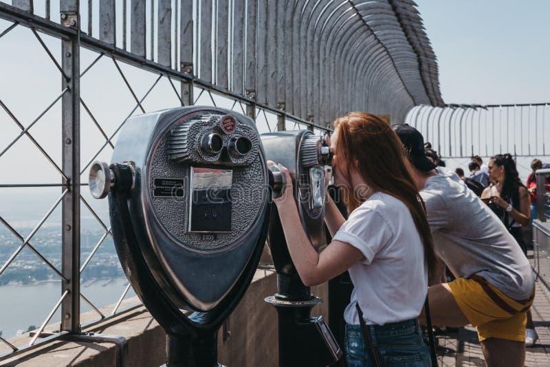 Посетители используя бинокли на платформе замечания на империи стоковое изображение rf