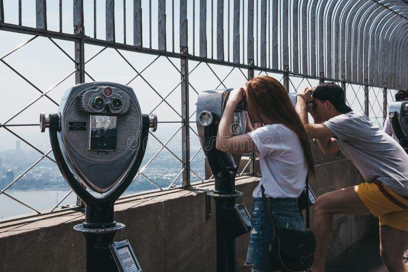 Посетители используя бинокли на платформе замечания на империи стоковая фотография rf