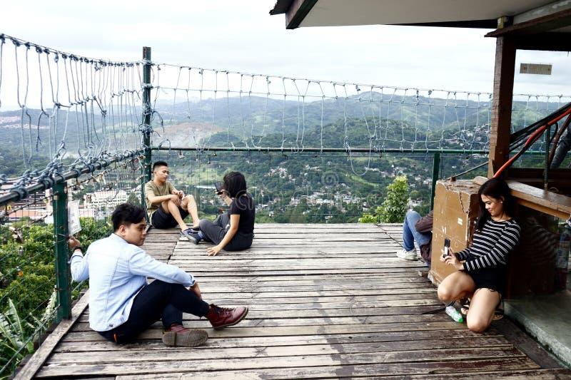 Посетители и туристы наслаждаются взглядом и прохладным ветерком вверху палуба просмотра 360 градусов стоковое фото