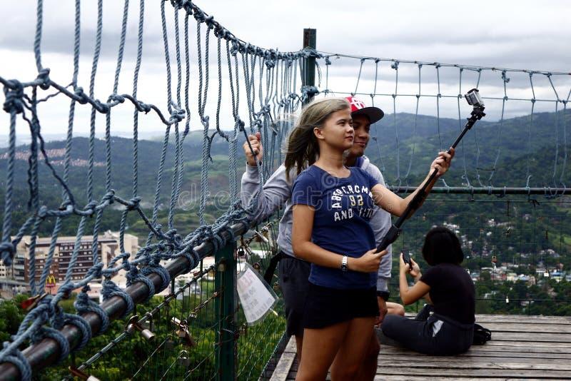 Посетители и туристы наслаждаются взглядом и прохладным ветерком вверху палуба просмотра 360 градусов стоковое фото rf