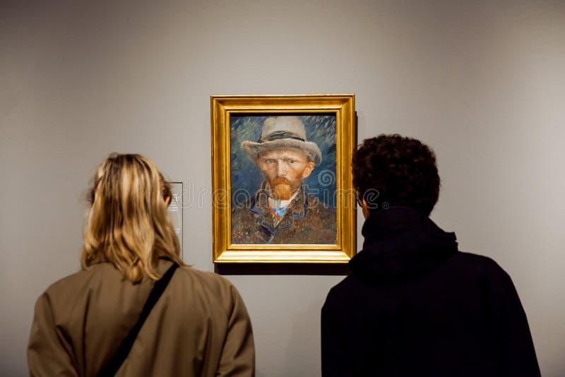 Посетители наблюдая художественное произведение автопортрета известного художника Винсента ван Гога в Rijsmuseum в городе Амстерд стоковая фотография rf