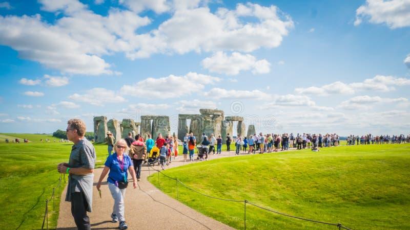 Посетители на наследии ЮНЕСКО Стоунхендж в Великобритании идя вокруг памятника стоковые фото