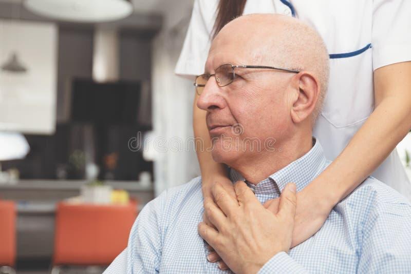 Посетитель здоровья и старший человек во время домашнего посещения стоковое изображение