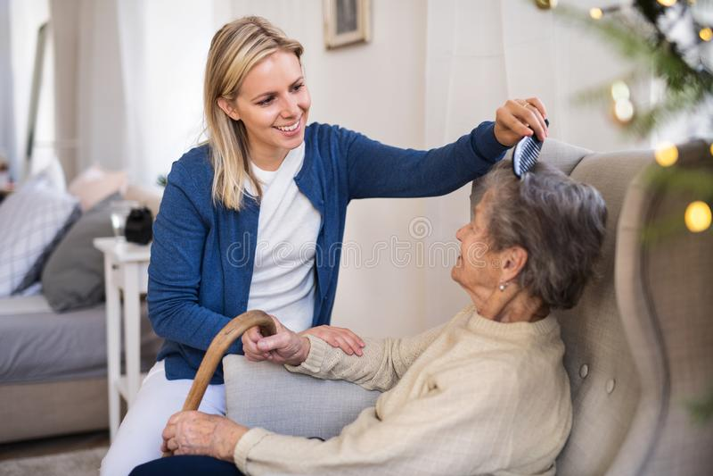 Посетитель здоровья расчесывая волосы старшей женщины дома на времени рождества стоковые изображения