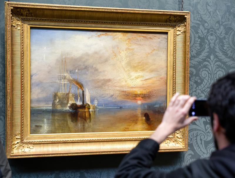 Посетитель смотря картину тернера Иосиф Mallord Вильям в национальной галерее в Лондоне стоковые фотографии rf