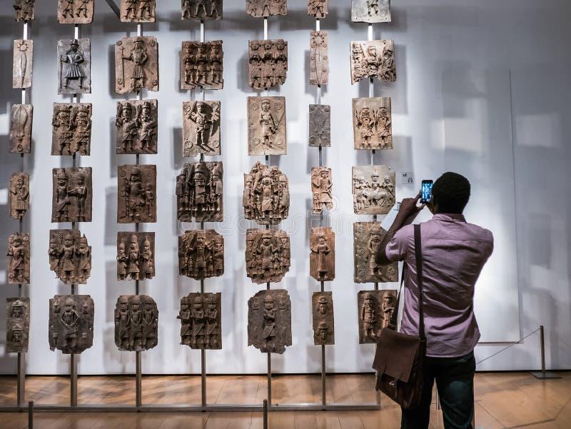 Посетитель великобританского музея фотографирует металлические пластинкы Бенина от Нигерии стоковые фотографии rf