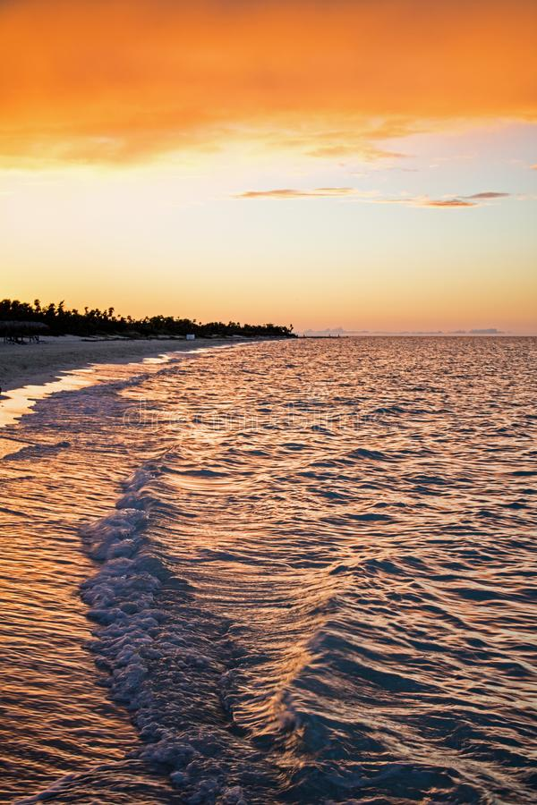 Последнее гениальное освещение дня на тропическом пляже стоковое фото