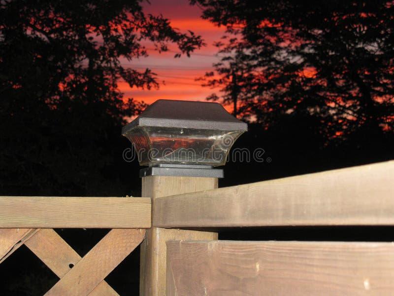 Последний заход солнца за светом столба загородки стоковое изображение