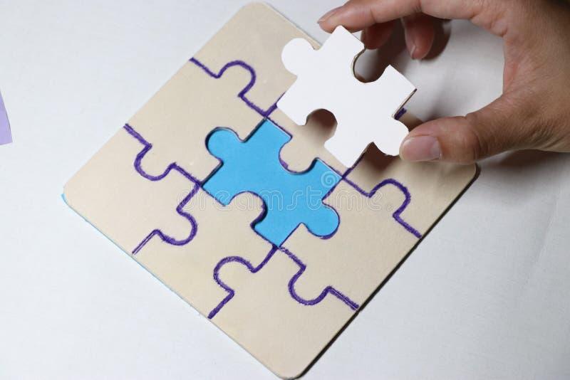 Последний кусок головоломки приближая к предпосылке белизны завершения стоковая фотография rf