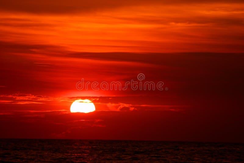 последний светлый заход солнца на луче облака неба оранжевом вокруг солнца над морем стоковые изображения rf