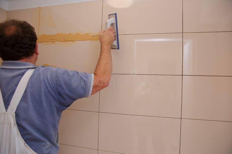 После класть плитки на стену, вы должны заполнить пространства между плитки, особенная масса цемента или фуга стоковые фото