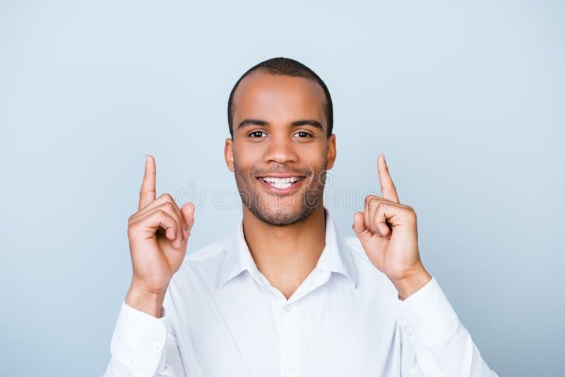 Посмотрите вверх! Молодой человек мулата с испуская лучи улыбкой указывает вверх по острословию стоковое изображение