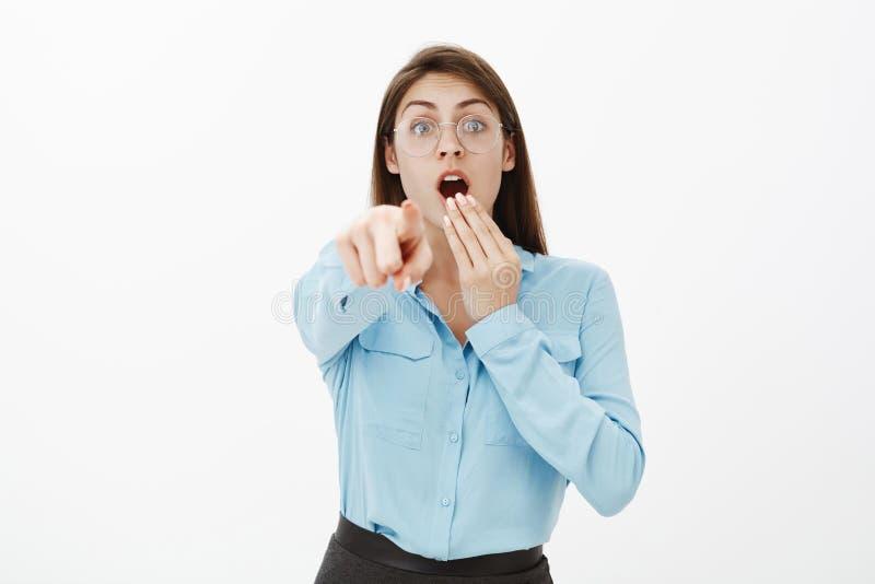 Посмотрите там, оно невероятный Shocked возбудил смешную женщину в стеклах и голубой блузке, покрывая раскрытый рот с рукой стоковое изображение rf