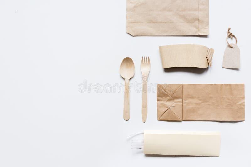 Поставка еды с бумажными сумками и flatware на сером модель-макете взгляд сверху предпосылки таблицы стоковые изображения rf