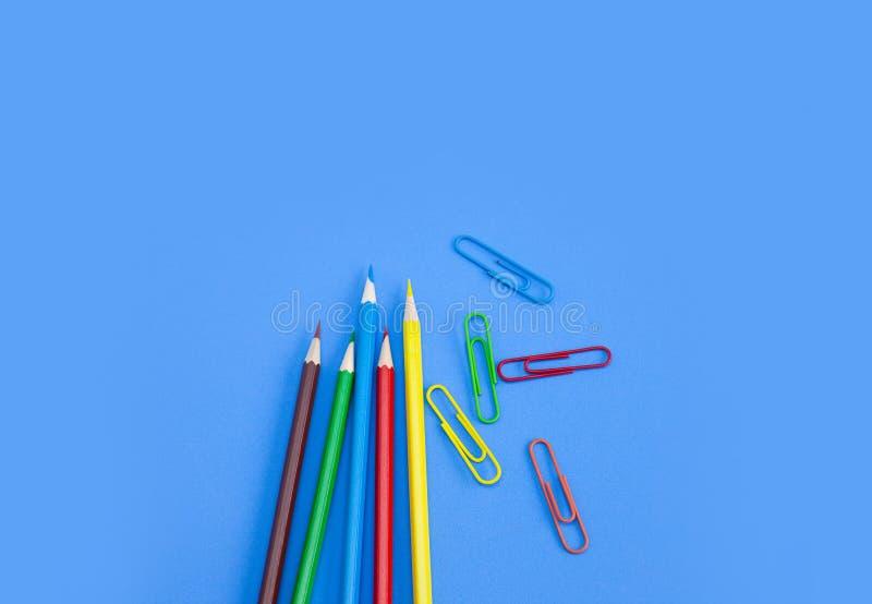 Поставки государственной канцелярии, покрашенные карандаши с красочными зажимами на голубой предпосылке стоковые изображения rf