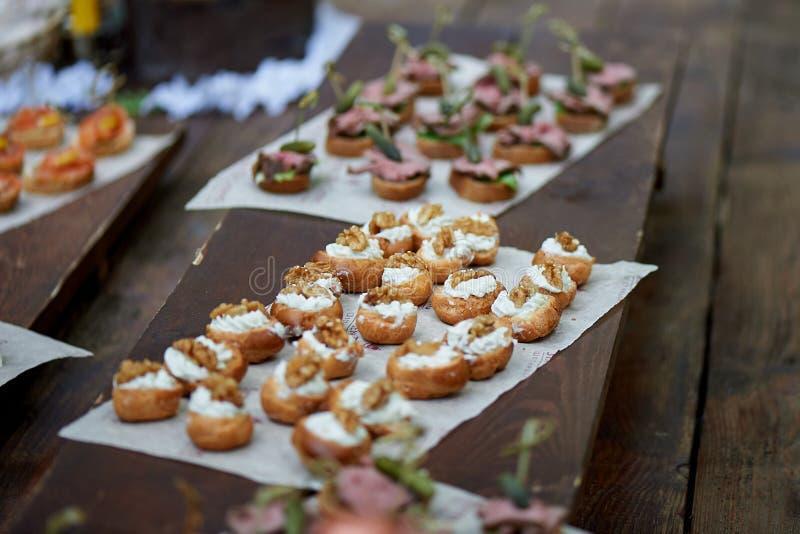 Поставлять еду для банкета свадьбы Канапе, малые сандвичи на бумажной и деревянной поверхности стоковое фото