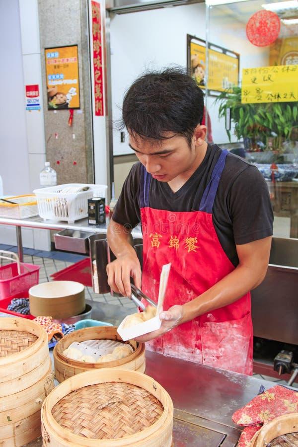 Поставщик еды улицы в Kaohsiung, Тайване, подготавливая испаренный Xiao длинное Bao, блюдо традиционного китайския изобретенное в стоковая фотография rf