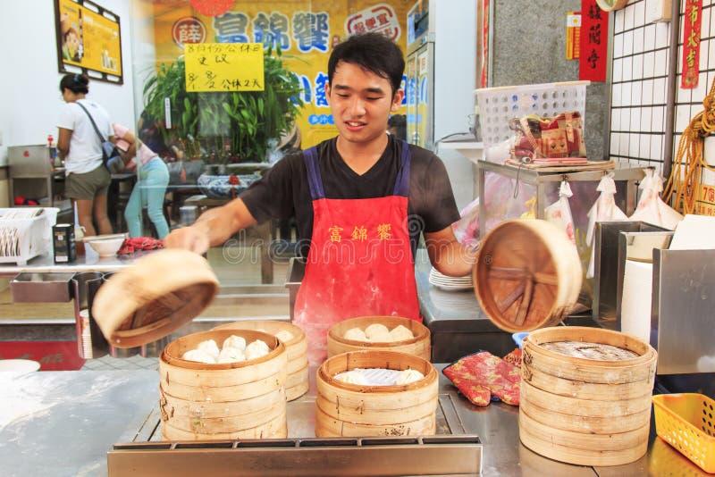 Поставщик еды улицы в Kaohsiung, Тайване, подготавливая испаренный Xiao длинное Bao, блюдо традиционного китайския изобретенное в стоковое фото