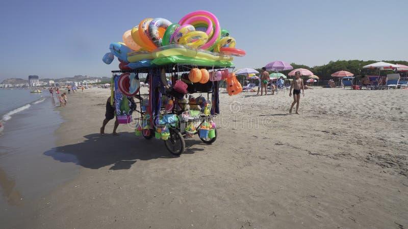 Поставщик продает купальник и игрушки к детям на пляже стоковое изображение rf