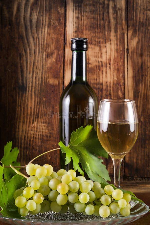 Поставьте зеленые виноградины и белое вино на обсуждение в стеклянной и черной бутылке украшенной с лозой стоковые фотографии rf