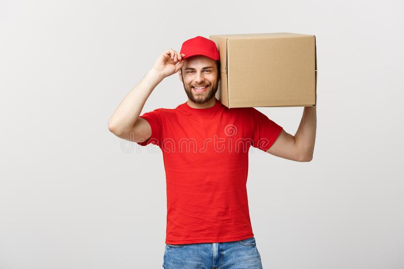 Поставьте концепцию: Молодой кавказский красивый работник доставляющий покупки на дом держа коробку на плече Изолировано над серо стоковые изображения