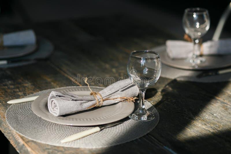 Поставьте установку на обсуждение Пары опорожняют серые плиты Нож и вилка Старомодные бокалы Деревенская салфетка таблица деревян стоковая фотография rf