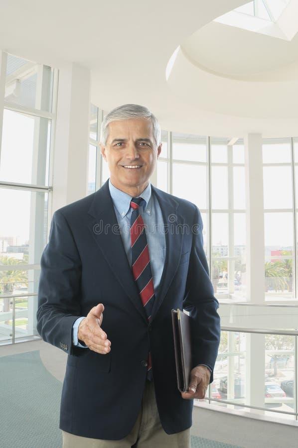 постаретая середина рукопожатия бизнесмена блейзера голубая стоковые изображения rf