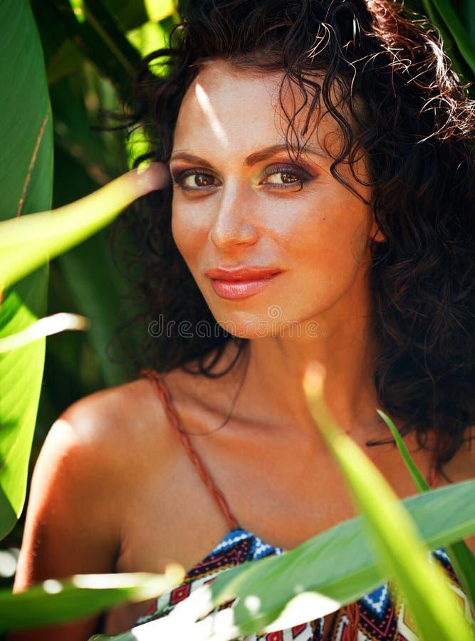 Постаретая серединой женщина брюнет элегантная с зелеными лист в экзотической стороне конца джунглей вверх усмехаясь, концепции л стоковая фотография rf