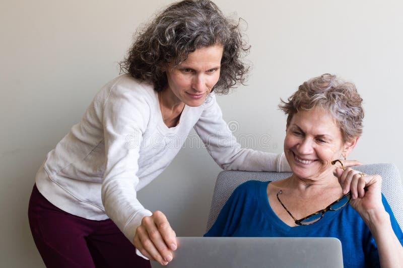 Постаретая серединой мать дочери помогая более старая стоковое фото