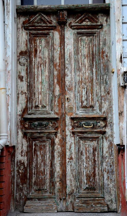 Постаретые выдержанные деревянные входные двери с краской шелушения стоковое фото rf