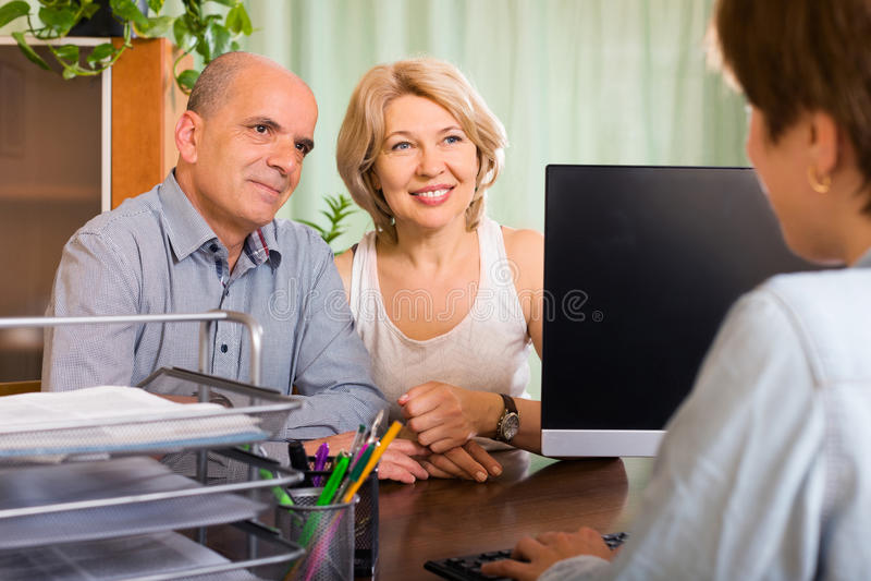 Постаретые пары пенсионеров разговаривая с работником стоковые изображения