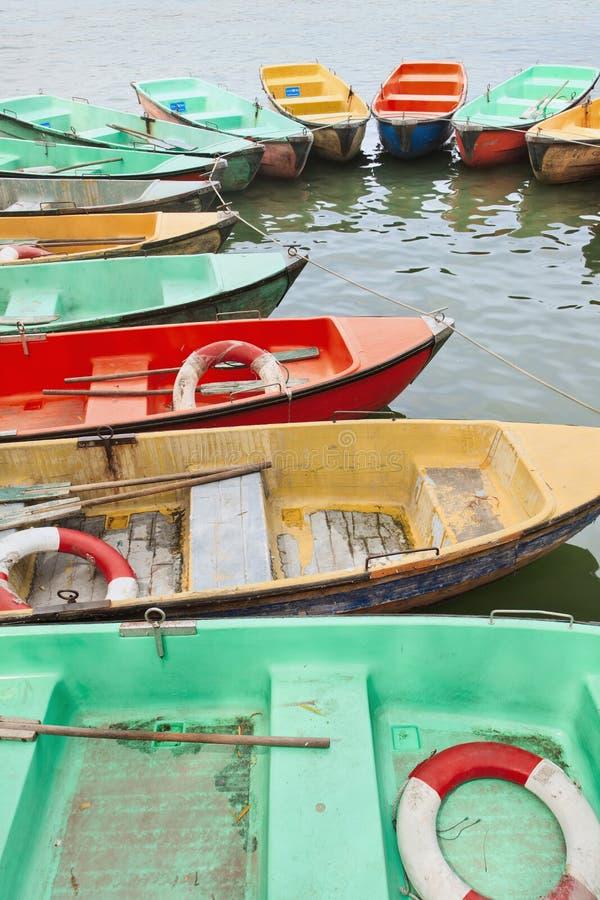 Постаретые multi покрашенные шлюпки строки причалили в озере стоковые изображения rf