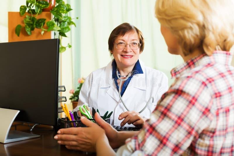 Постаретый доктор имея хорошие новости для пациента стоковая фотография