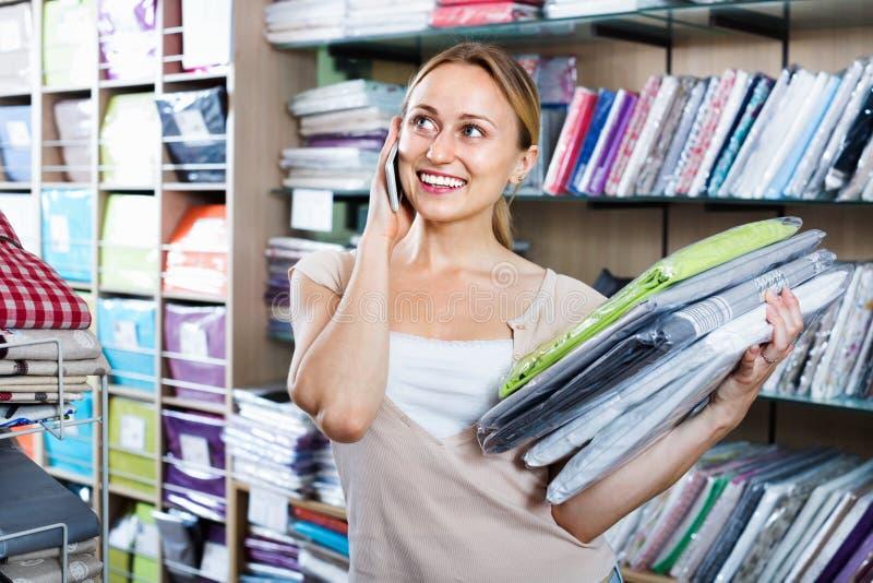 Постельные принадлежности молодой женщины покупая установленный магазин и говорить на мобильном телефоне стоковая фотография