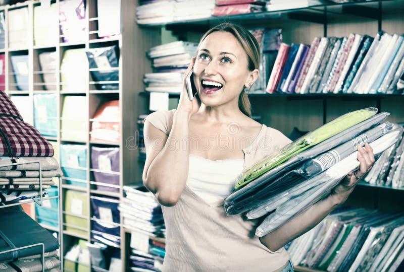 Постельные принадлежности молодой женщины покупая установленный магазин и говорить на мобильном телефоне стоковая фотография rf