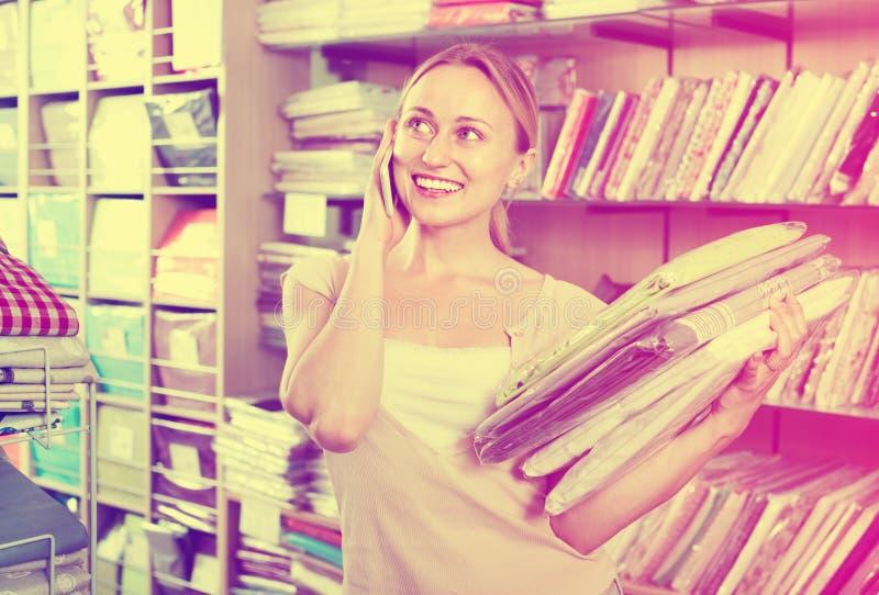 Постельные принадлежности молодой женщины покупая установленный магазин и говорить на мобильном телефоне стоковое фото