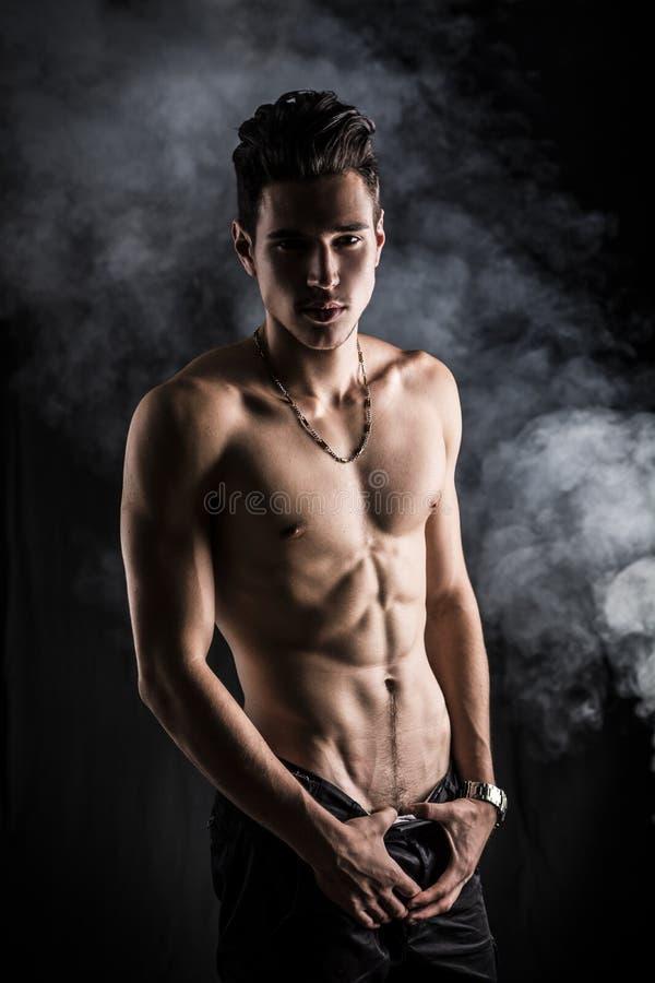 Постный атлетический без рубашки молодой человек стоя на темной предпосылке стоковое фото rf