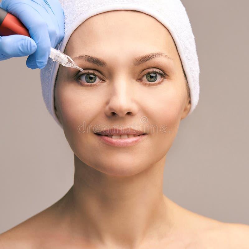 Постоянная татуировка макияжа Забота кожи стороны женщины Mikrobleyding Cosmetologist женский стоковая фотография rf