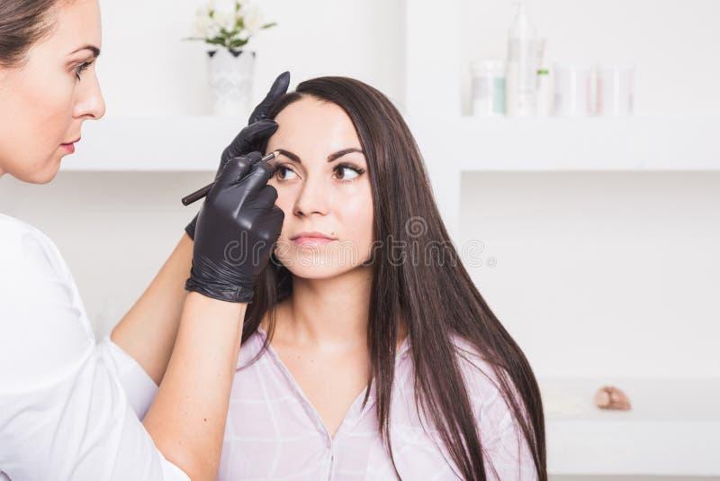 Постоянный макияж для бровей красивой молодой женщины в салоне красоты стоковое фото rf