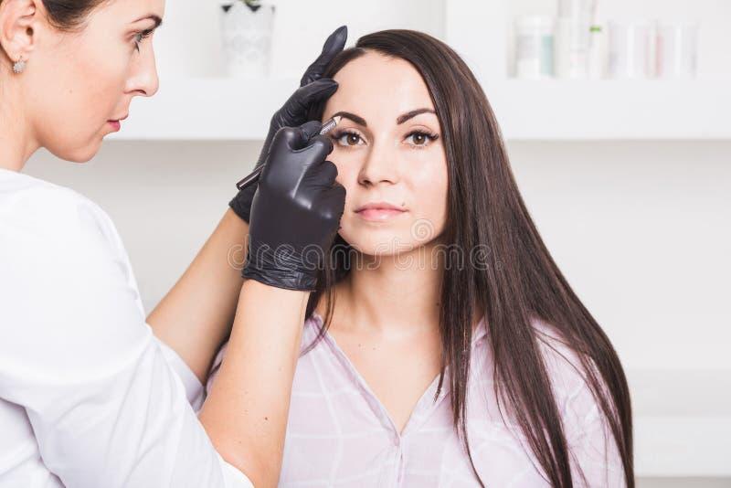 Постоянный макияж для бровей красивой молодой женщины в салоне красоты стоковые фотографии rf