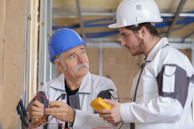 Построители используя желтый вольтамперомметр для того чтобы откалибрировать дом стоковая фотография rf