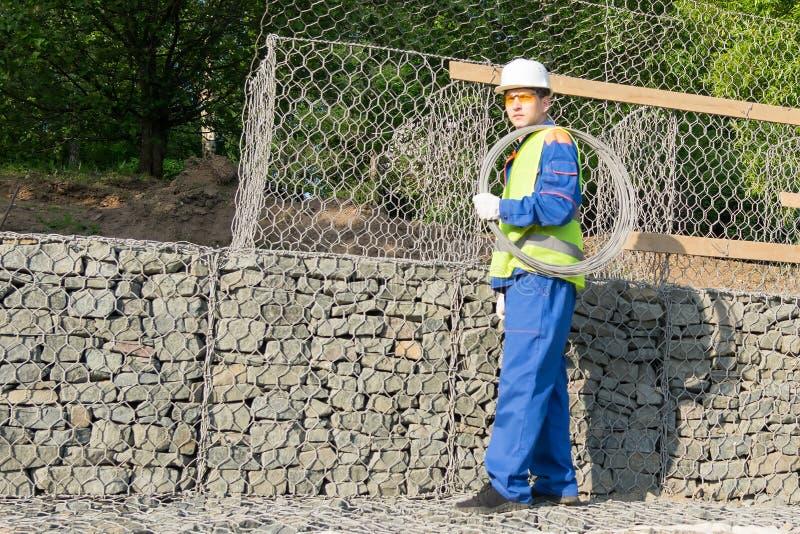 Построитель в прозодеждах носит большое пасмо провода на его плече, взгляда со стороны стоковое изображение
